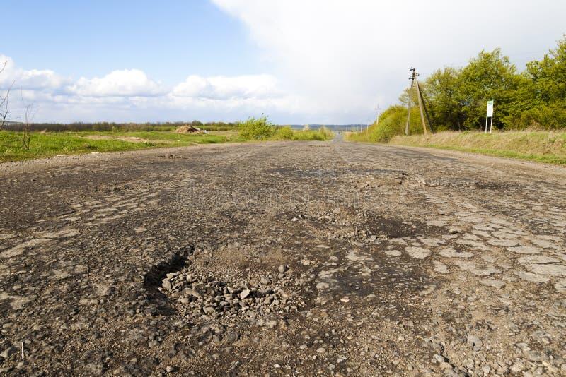 Beschadigde landelijke weg, gebarsten asfalt blacktop met potholes en p royalty-vrije stock afbeeldingen