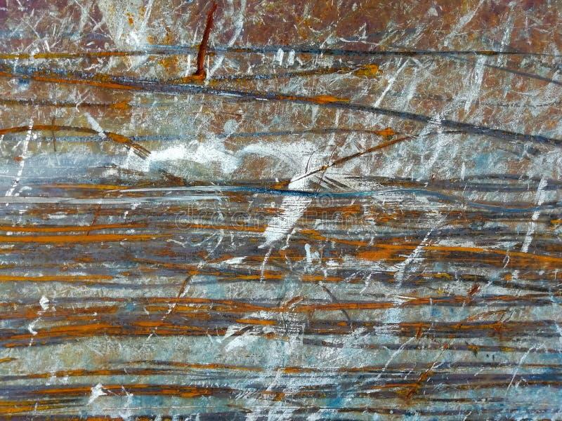 Beschadigde metaaloppervlakte met oranje en blauwe horizontale krastekens stock afbeeldingen