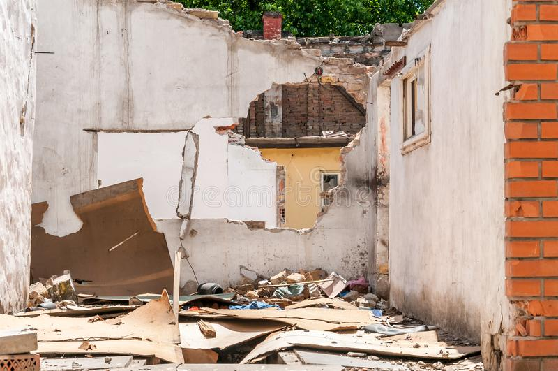 Beschadigde muur van binnenlands burgerlijk huis of de bouw met gat en doen ineenstorten die dak door granaat in de oorlogsstreek stock fotografie