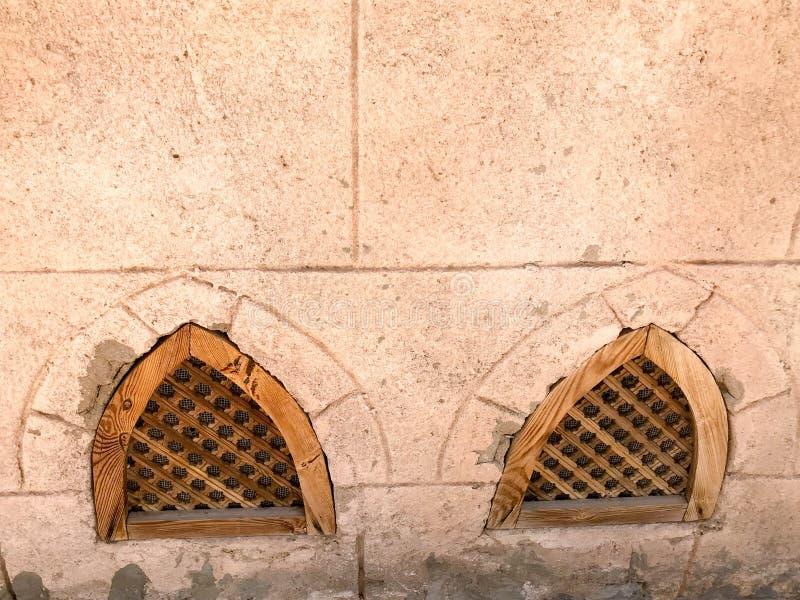 Beschaffenheit der alten alten gelben starken Steinwand mit Fenstern von hölzernen Fensterläden von unterhalb im arabischen islam stockfotos