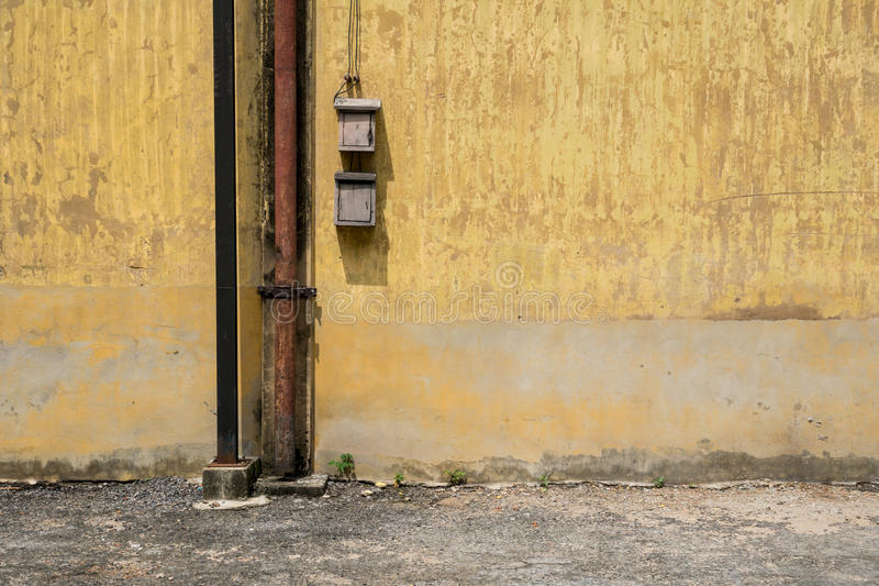 Beschaffenheit der alten gelben Weinlesewand der industriellen Fabrik mit verrostetem Eisenpfosten und elektrischer Leitung stockbild