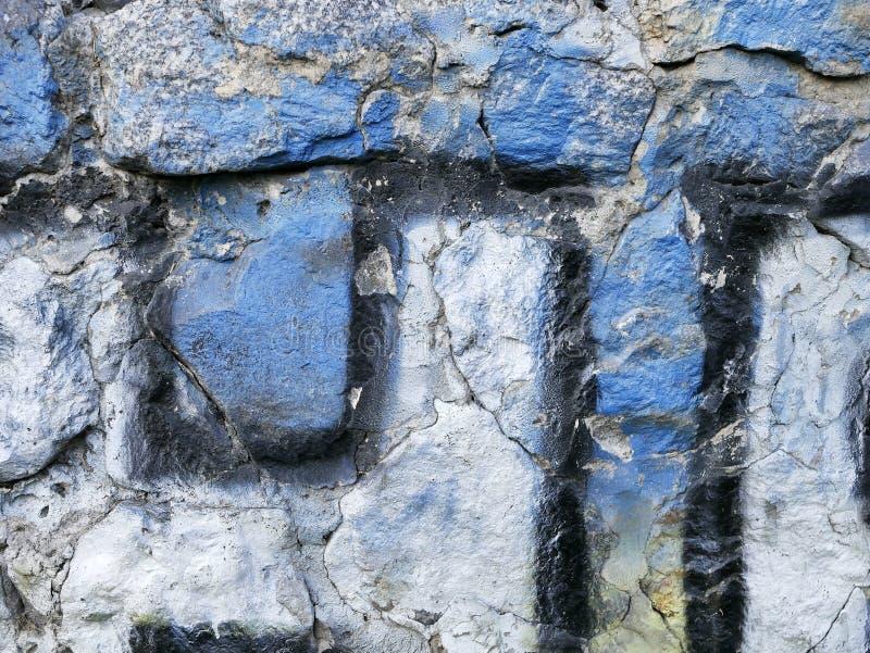 Beschaffenheit der alten Steinwand abstrakt gemalt mit blauer, grauer, schwarzer Farbe lizenzfreies stockbild