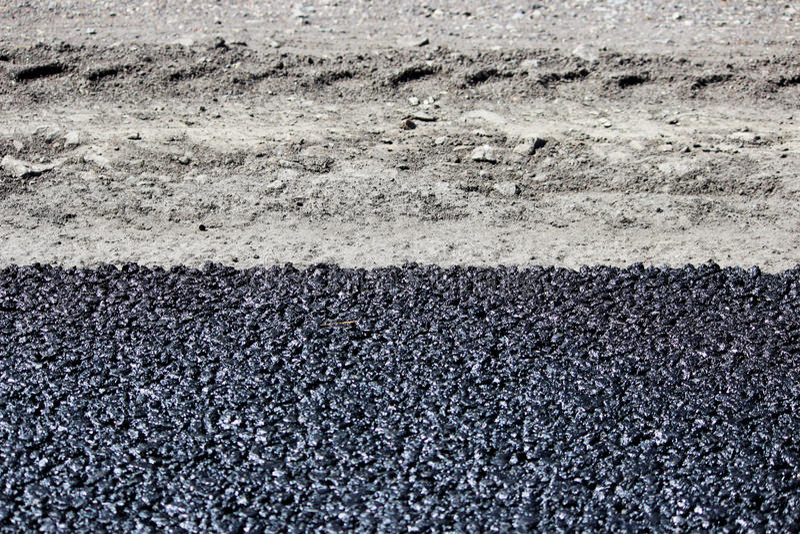 Beschaffenheit des frischen heißen schwarzen Asphalts wird auf die neue Straße nahe der Straßenrand- und Autobahn gelegt lizenzfreies stockbild