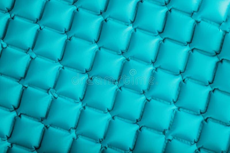 Beschaffenheit einer blauen aufblasbaren touristischen Wolldecke, Abschnitte und Muster wiederholend Ultralight portierbare Wolld stockfotografie