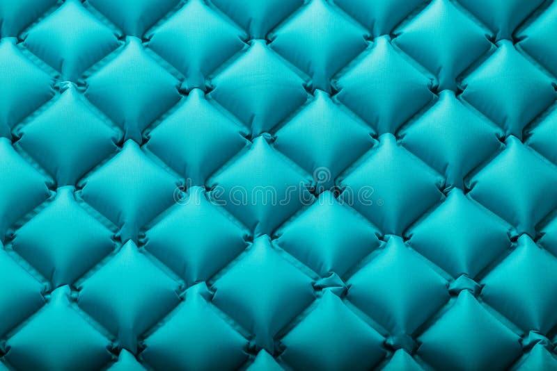 Beschaffenheit einer blauen aufblasbaren touristischen Wolldecke, Abschnitte und Muster wiederholend Ultralight portierbare Wolld lizenzfreies stockfoto