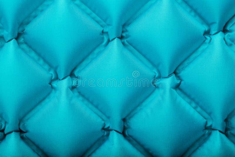 Beschaffenheit einer blauen aufblasbaren touristischen Wolldecke, Abschnitte und Muster wiederholend Ultralight portierbare Wolld stockfoto