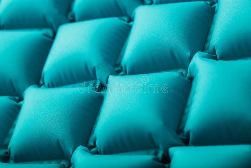 Beschaffenheit einer blauen aufblasbaren touristischen Wolldecke, Abschnitte und Muster wiederholend Ultralight portierbare Wolld lizenzfreie stockfotografie