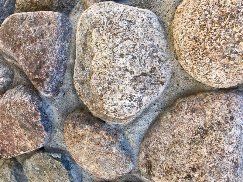 Beschaffenheit von natürlichen geschnitzten festen starken rauen strukturierten grauen braunen Steinkopfsteinmineralwänden des Fe lizenzfreie stockfotos