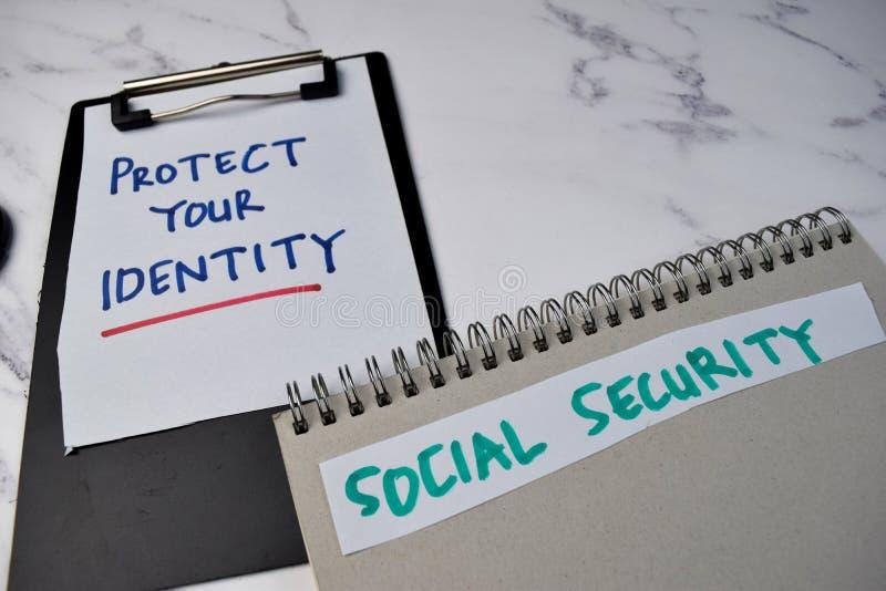 Bescherm Uw Identiteit en Sociale Zekerheid schrijven op een boek dat op het Bureau van het Bureau wordt geïsoleerd royalty-vrije stock afbeelding