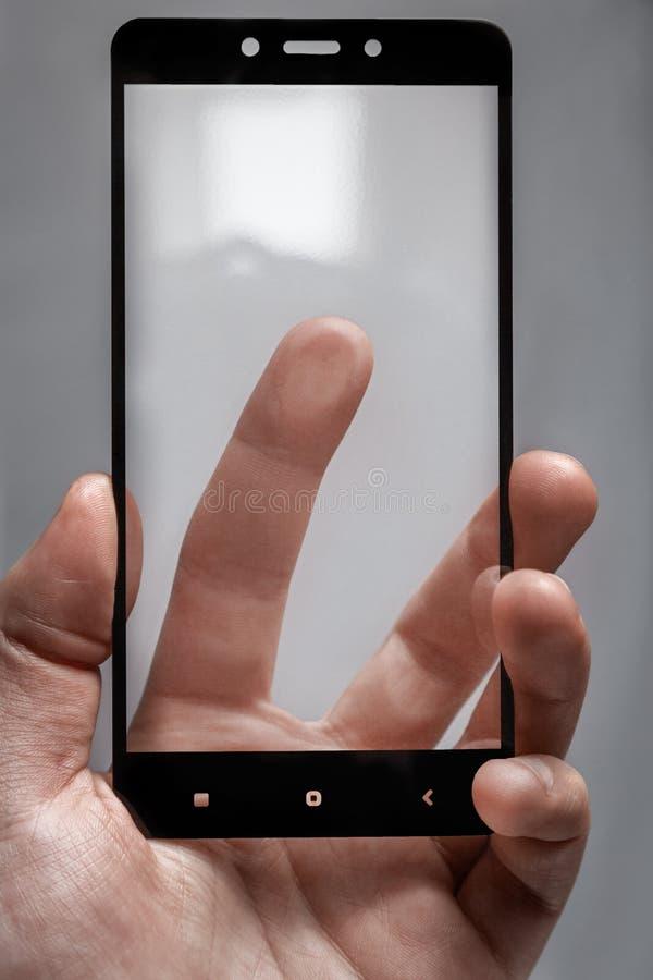 Beschermend glas voor telefoon in mannelijke hand en vinger wat betreft de het schermoppervlakte stock afbeeldingen
