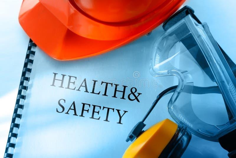Beschermende brillen, oortelefoons en rode helm stock fotografie