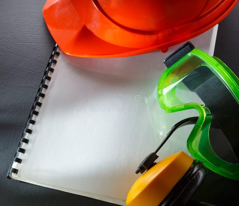 Beschermende brillen, oortelefoons en rode helm stock afbeeldingen