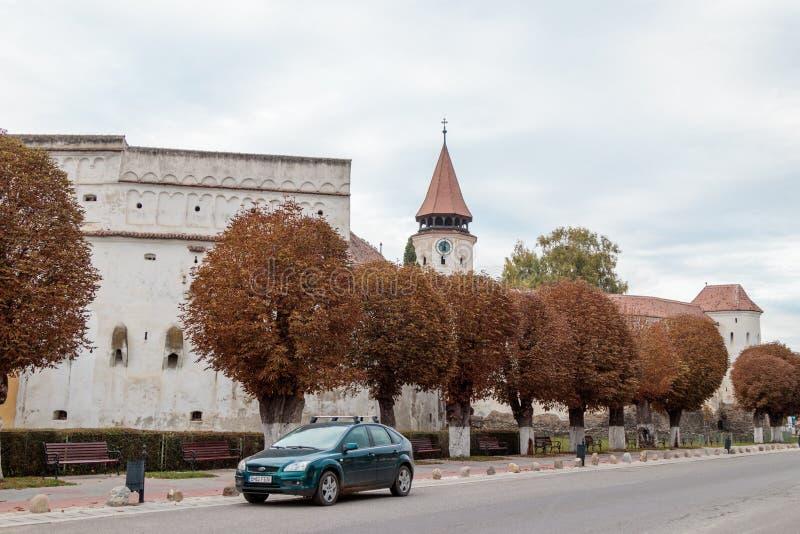 Beschermende muren en watchtower met de klok van de Versterkte Kerk Prejmer in Prejmer-stad in Roemenië stock foto's
