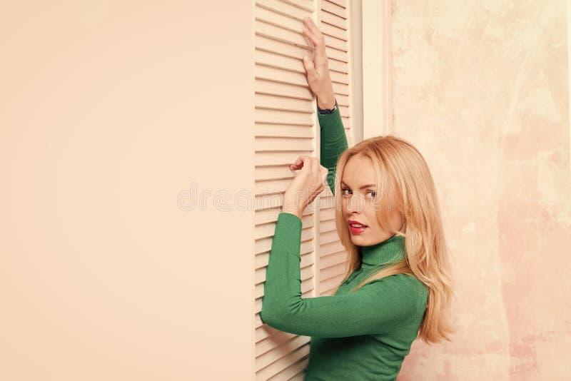 Bescherming en comfort Zoet huisconcept, exemplaar ruimtemeisje in het groene sweater stellen bij vensterblinden stock foto's