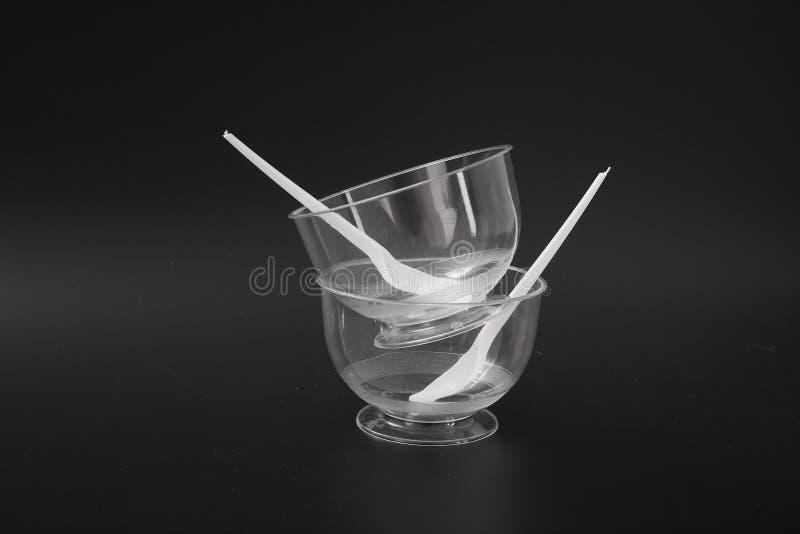 Beschikbaar plastic keukengerei op een zwarte achtergrond Roomijskom royalty-vrije stock foto