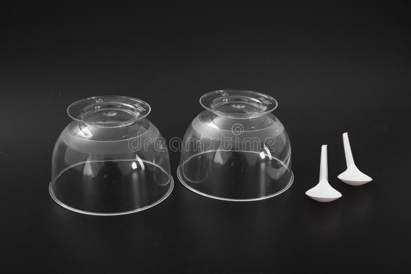 Beschikbaar plastic keukengerei op een zwarte achtergrond Roomijskom royalty-vrije stock foto's