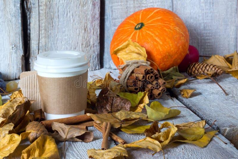 Beschikbare koffiekop met de herfst gele bladeren op houten achtergrond als achtergrond Het seizoenconcept van de herfst Handen d stock afbeeldingen