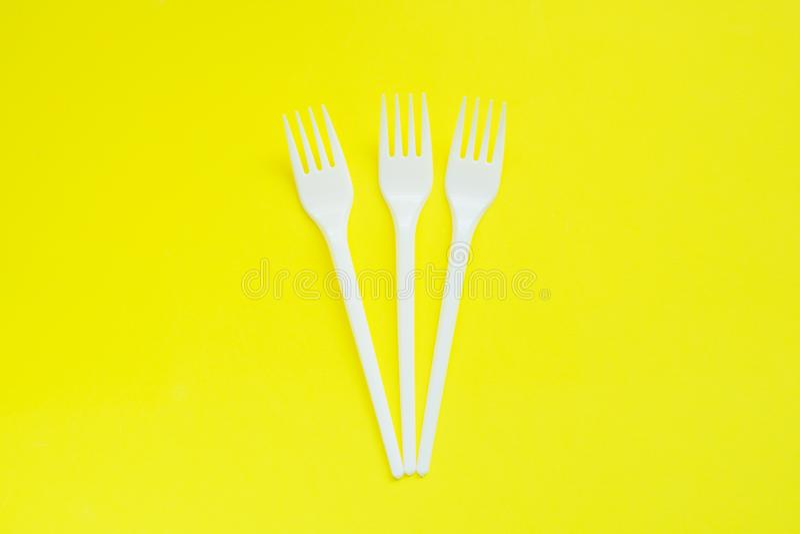 Beschikbare plastic stoppen op heldere gele achtergrond met exemplaarruimte stock afbeelding