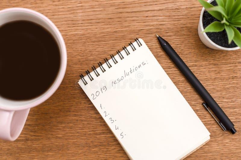 Beschlüsse der Draufsicht 2019 listen mit Notizbuch, Tasse Kaffee auf hölzernem auf stockbild