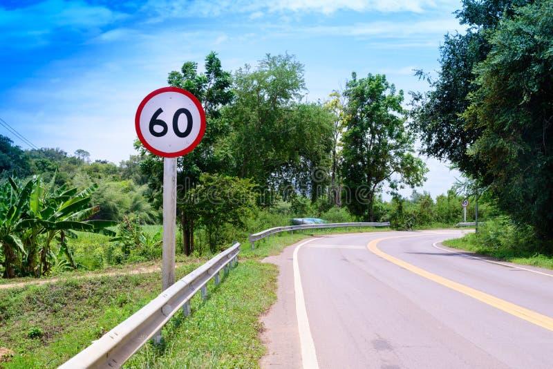 Beschleunigen Sie begrenztes Warnzeichen 60km/h gegen einen Hintergrund des blauen Himmels stockfotografie