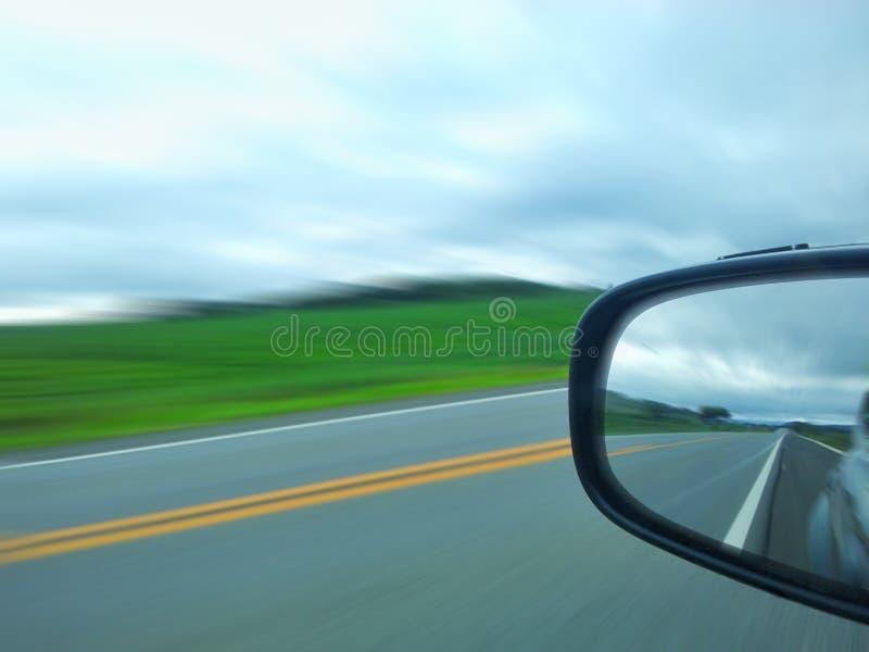 Beschleunigen Sie Landstraße auf dem äußeren Spiegel des Autos lizenzfreie stockbilder