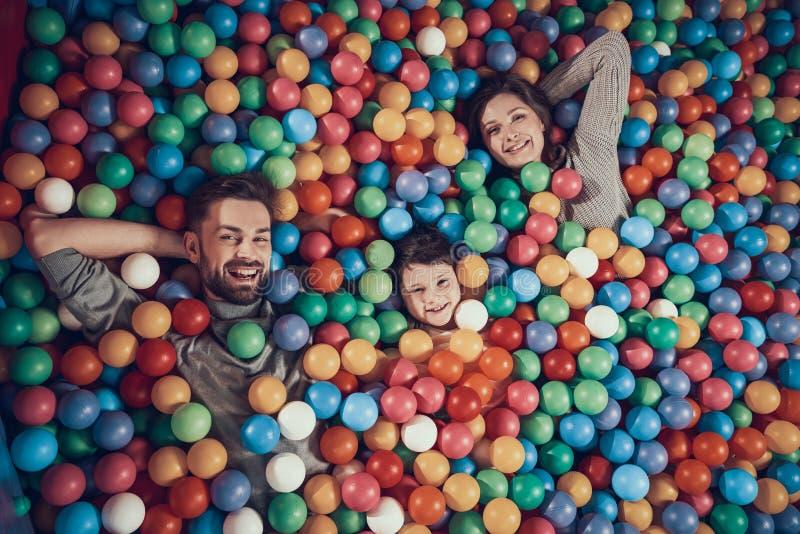 Beschneidungspfad eingeschlossen Glückliche Familie, die im Pool mit Bällen liegt lizenzfreies stockbild