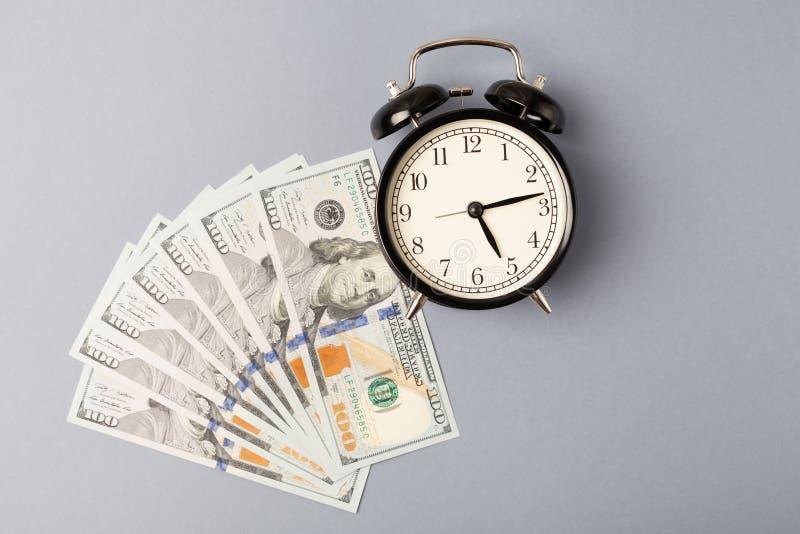 Beschneidungspfad eingeschlossen Schwarzer Metallwecker auf einem Stapel von Dollarbanknoten Flache Lage Zeit, Geld zu verdienen  stockfotos