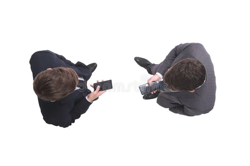 Beschneidungspfad eingeschlossen zwei Geschäftsmänner, welche die Schirme ihrer Smartphones betrachten stockbild