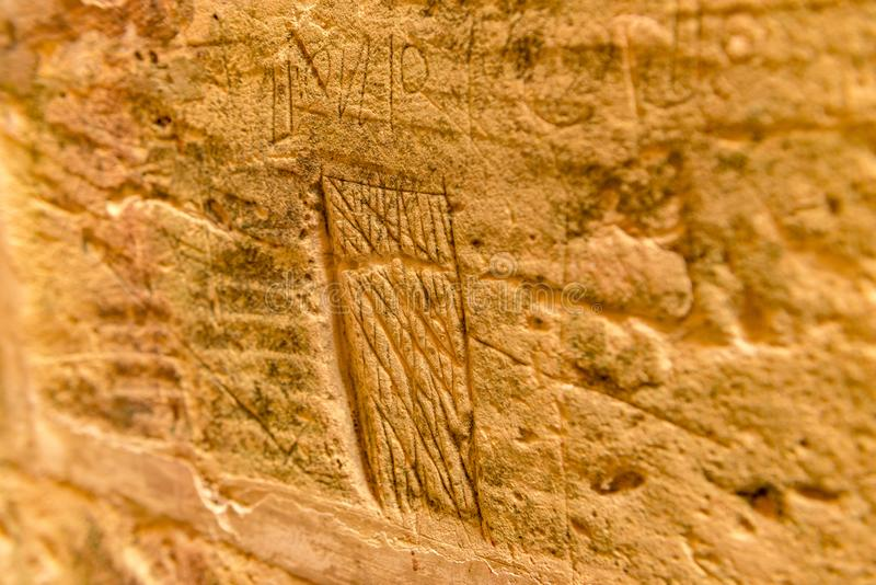 Beschreibung des Malteser Kreuzes auf der Wand der Zelle im alten Gefängnis von Rabat-Zitadelle, in Victoria lizenzfreies stockfoto