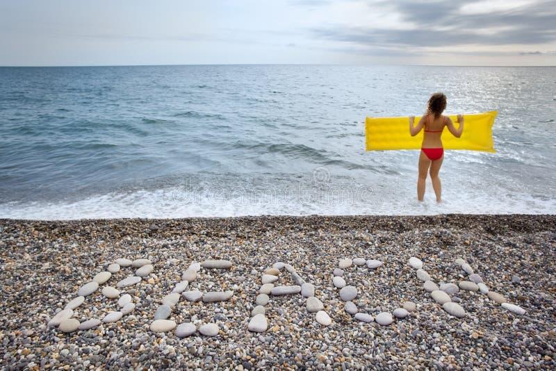 Beschreibung von den Steinen SETZEN an der Küste und an der Frau auf den Strand lizenzfreie stockbilder