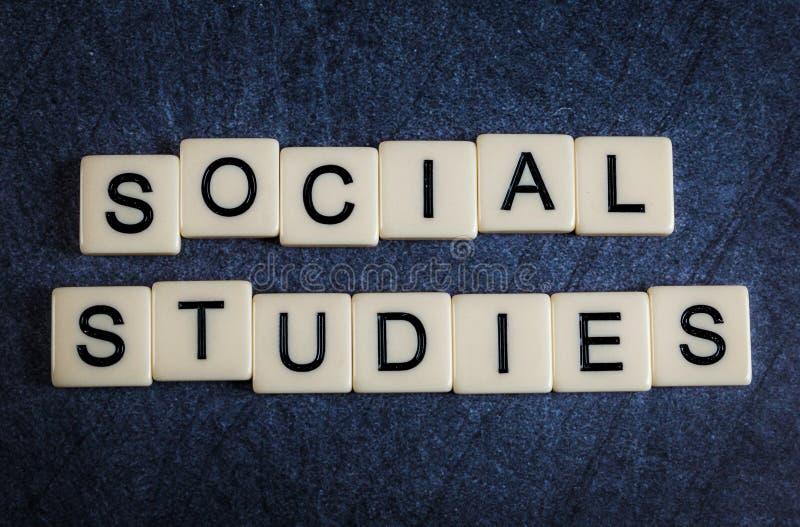 Beschriften Sie Fliesen auf dem schwarzen Schieferhintergrund, der Sozialstudien buchstabiert stockfotos