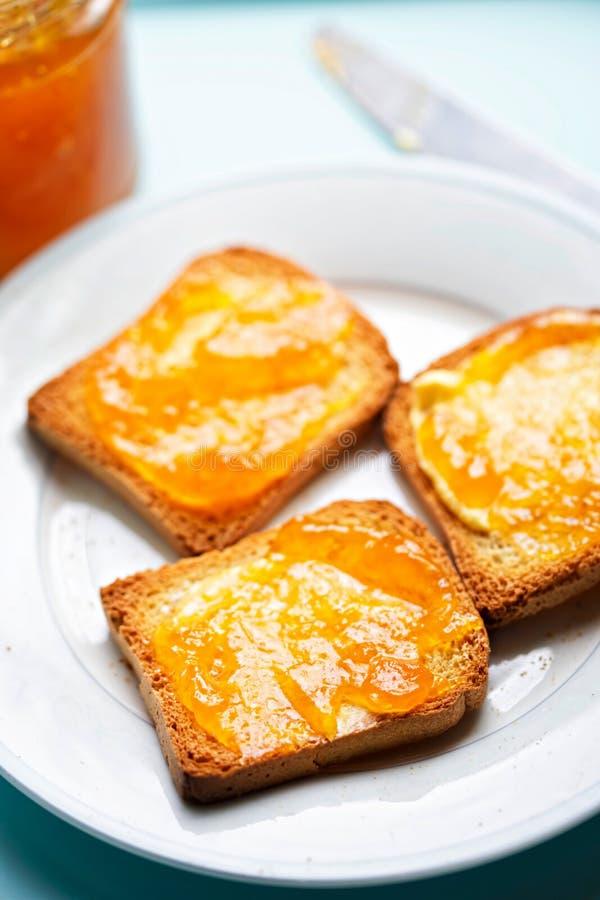 Beschuit met abrikozenjam op blauwe oppervlakte royalty-vrije stock afbeelding
