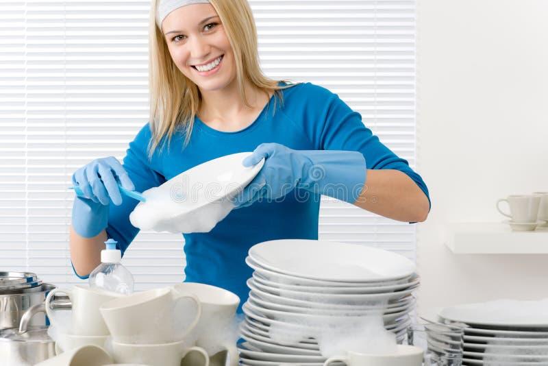 besegrar den moderna tvättande kvinnan för lyckligt kök royaltyfri foto