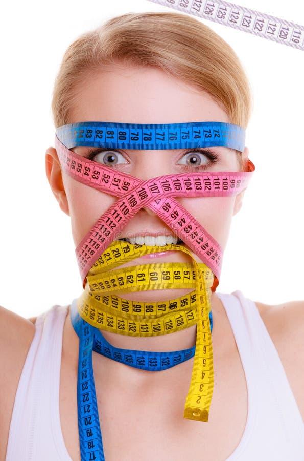 Besessen gewesene sportliche Sitzfrau mit Maßbändern Zeit für das Diätabnehmen lizenzfreies stockbild