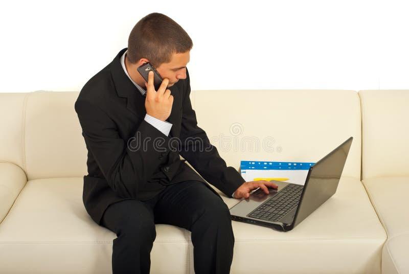 Besetzter Geschäftsmann, der auf Sofa sitzt stockfotos