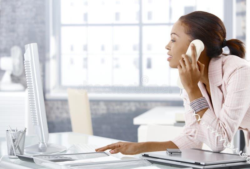 Besetztes Büromädchen am Telefon stockbild