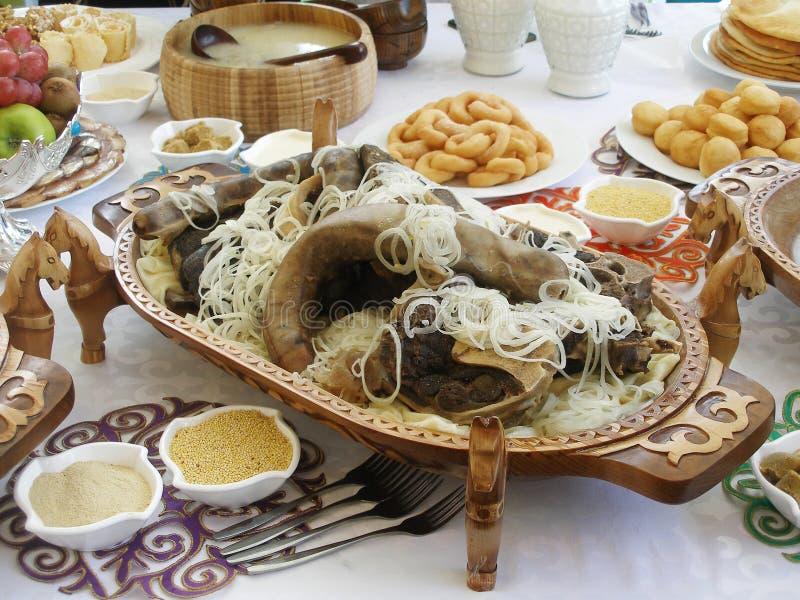 Beshbarmak - блюдо казаха национальное на высекаенном деревянном диске праздничная таблица стоковые изображения