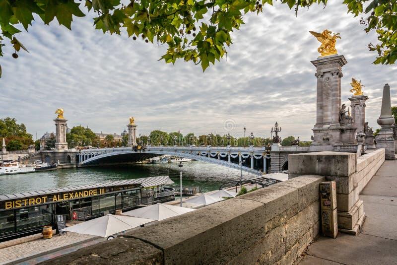 Beskåda att se över den utsmyckade Alexander III bron in mot den storslagna Palaisen i Paris fotografering för bildbyråer