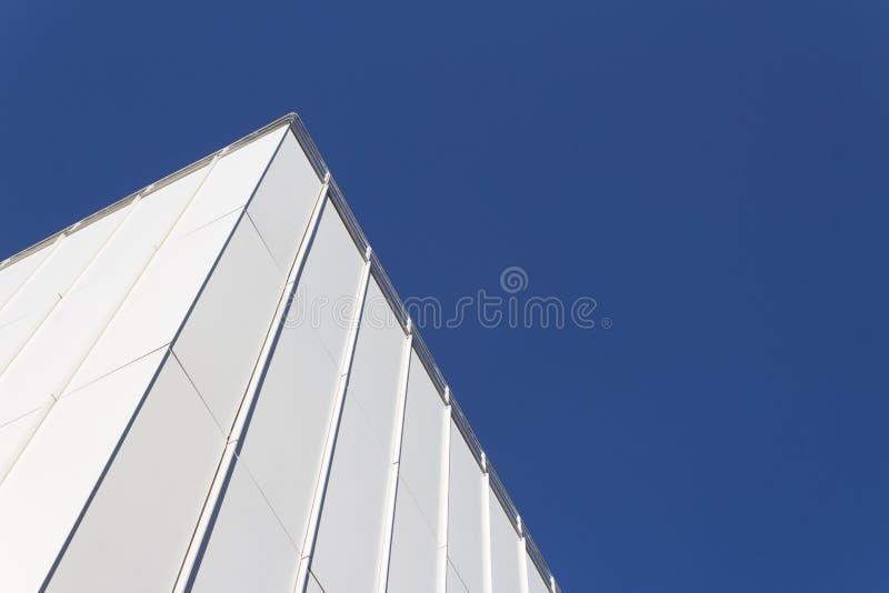 Beskåda att se upp på hörnet av den vita generiska byggnadsfasaden mot en mycket djupblå himmel arkivbild