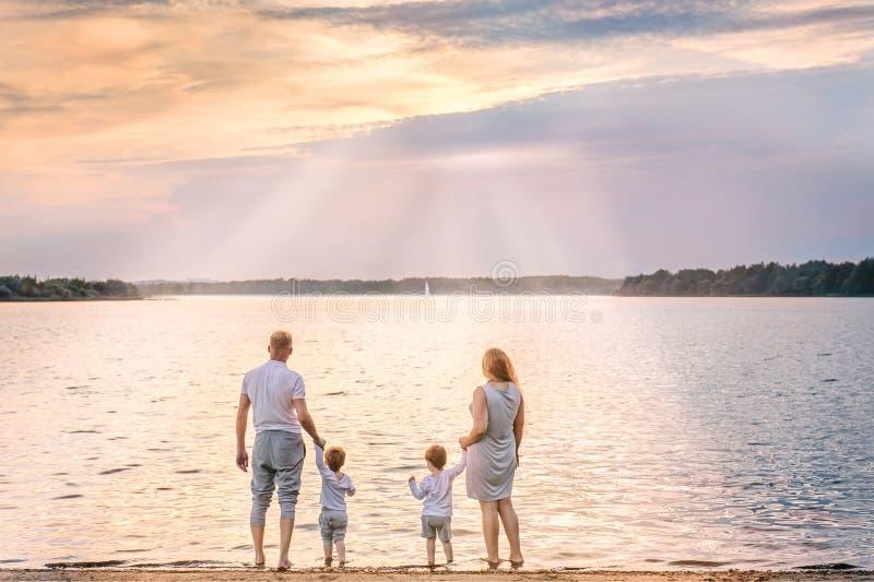 Beskåda bakifrån av den lyckliga familjen som håller ögonen på solnedgången och sailboaen fotografering för bildbyråer