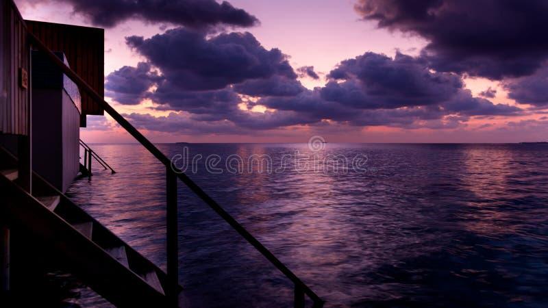 Beskåda en blåaktig och magentafärgad solnedgång som täckas med moln i den maldiviska ön royaltyfri foto