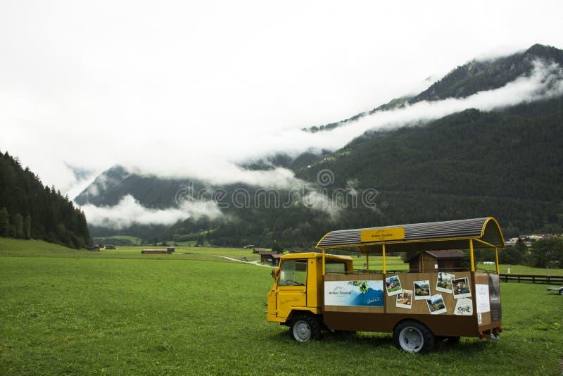 Beskåda landskapet och berget med den lilla lastbilen på ängar på Pfunds arkivfoton