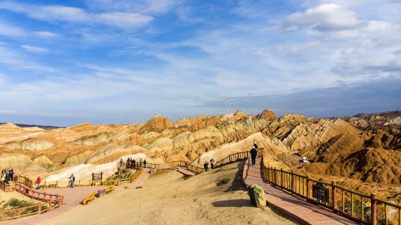 Beskåda plattformen och kinesiska turister Geologiska regnbågeberg parkerar Zhangye Danxia arkivbilder