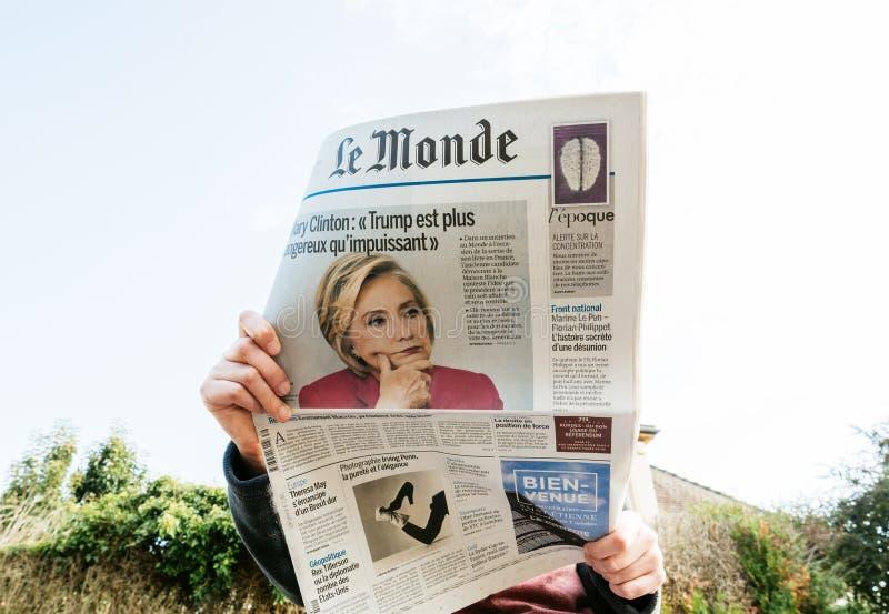 Beskåda underifrån av kvinnan som läser den senaste tidningsLe Monde med ståenden av Hillary Clinton royaltyfri foto