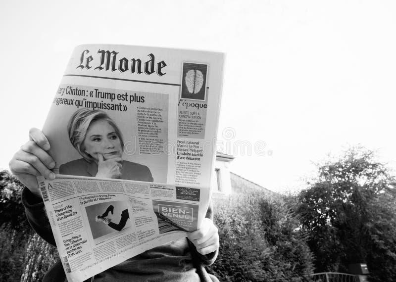 Beskåda underifrån av kvinnan som läser den senaste tidningsLe Monde med ståenden av Hillary Clinton royaltyfria foton