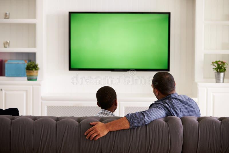 Beskådar hållande ögonen på TV för fadern och för sonen hemma tillsammans, tillbaka royaltyfri foto