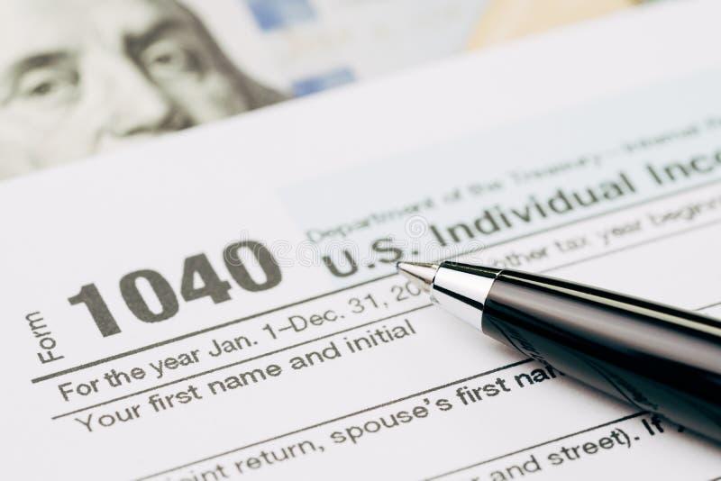 Beskatta tidbegreppet, selektiv fokus på penna på individ för 1040 USA I royaltyfri bild