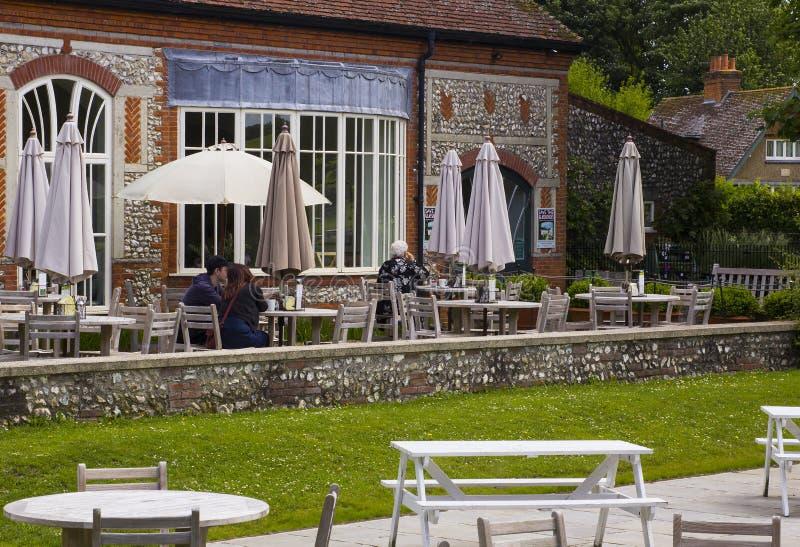 Beskyddare som dricker kaffe på terrassen av coffee shop på de berömda trädgårdarna i det västra dekangodset i Hampshire i södern royaltyfria foton