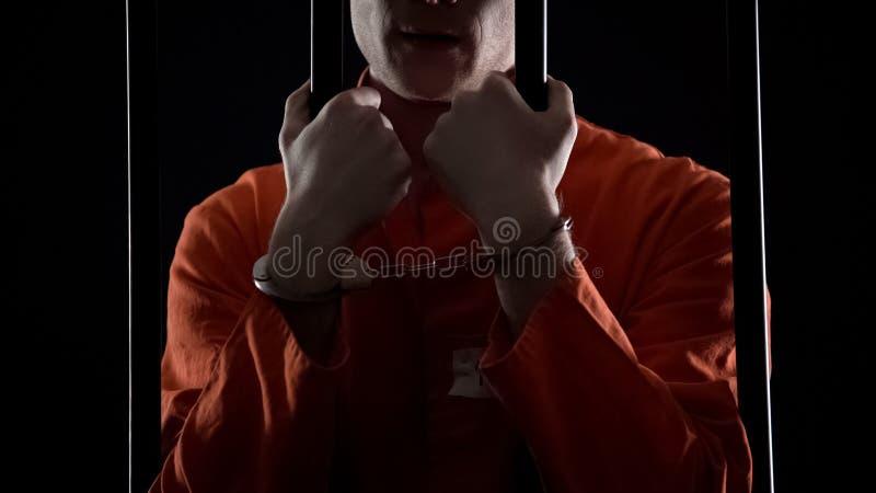 Beslagen man i handbojor som rymmer fängelsestänger, bestraffning för finansiellt bedrägeri royaltyfria bilder