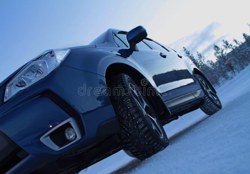 Beslagen sneeuwbanden op de auto bij de winterweg royalty-vrije stock afbeeldingen